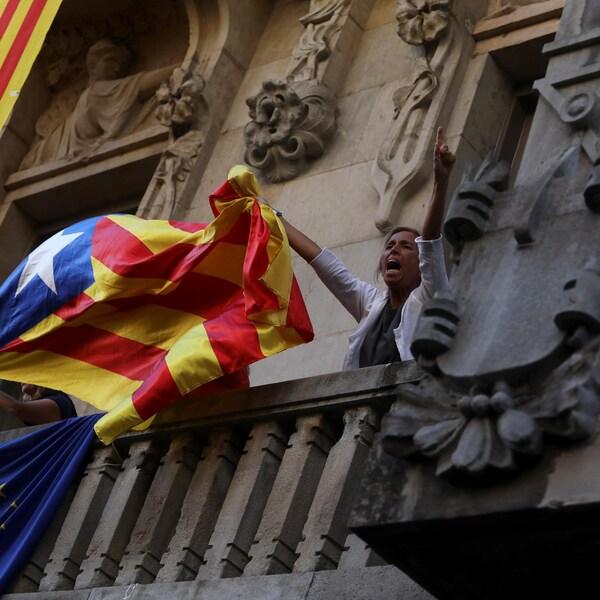 Une femme brandit un drapeau catalan lors d'une manifestation à Barcelone.