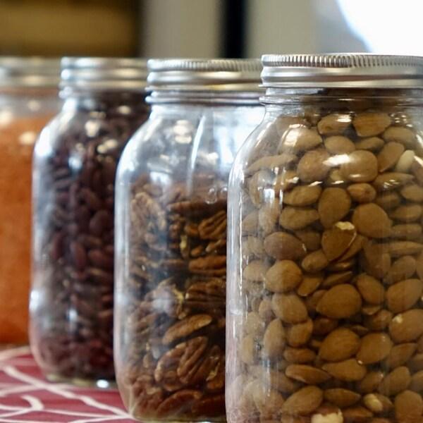 Gros plan sur plusieurs pots Masson alignés sur une table concernant différents types de noix et de légumineuses.