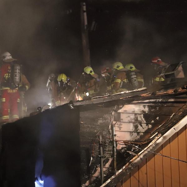 Des pompiers marchent sur le toit de la résidence.