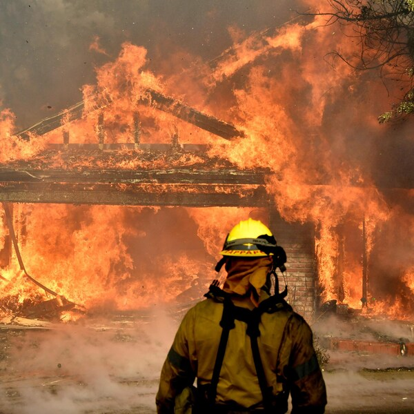 Un pompier devant une maison en flammes.