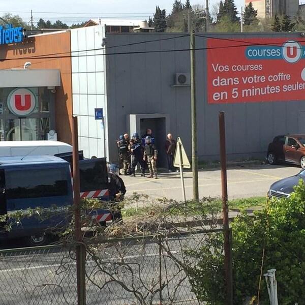 Des policiers près d'une porte de côté d'un bâtiment commercial.