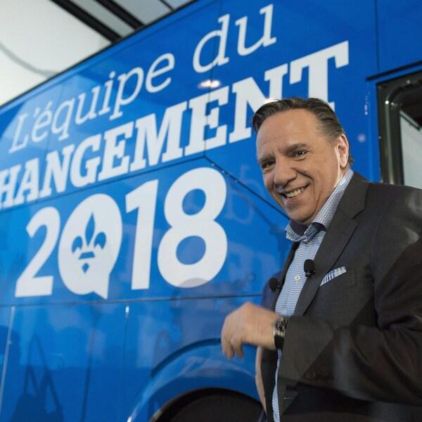 François Legault sourit pour les caméras alors qu'il se trouve devant l'autobus de la CAQ, sur laquelle est inscrit « L'équipe du changement 2018 ».