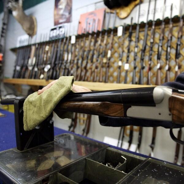 Un vendeur dans un magasin de chasse d'Ottawa essuie une arme d'épaule, devant un mur où sont présentées de nombreuses autres armes.