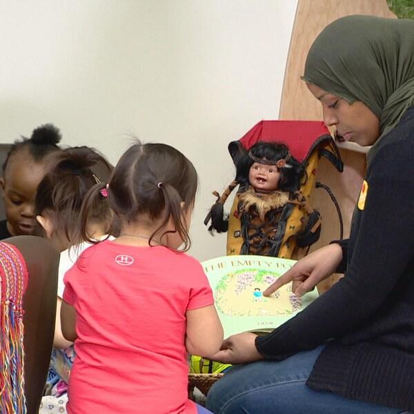 Une femme couverte d'un voile sur la tête (à droite) montre un livre à une fillette, de dos (à gauche), en arrière-plan, deux autres enfants et une poupée. Au total, l'Alberta comptera 122 garderies et centres d'expérience préscolaire subventionnés. La plupart se trouve à Calgary et Edmonton.