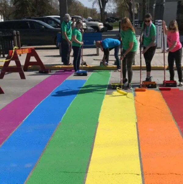 De gauche à droite on peut voir les couleurs : mauve, bleu, vert, jaune, orange et rouge qui sont en train d'être appliquées sur une rue par des gens.