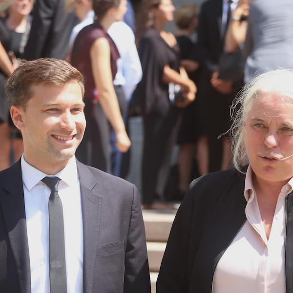 Un homme, souriant, et une femme à la sortie de la basilique-cathédrale, en plein soleil.