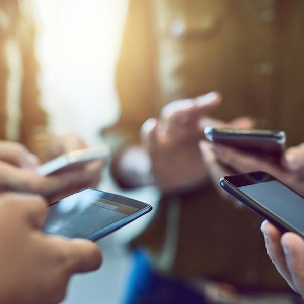 Un groupe de personnes en train d'utiliser leur cellulaire.