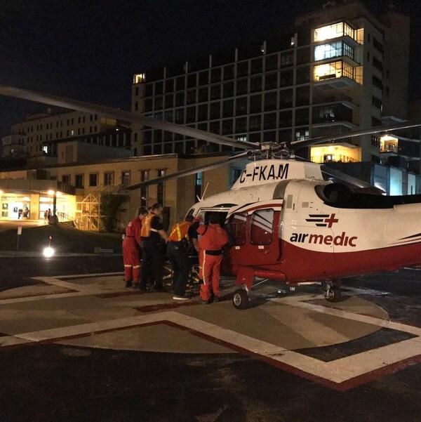 Un hélicoptère de l'entreprise Airmedic se dépose près d'un hôpital en pleine nuit.