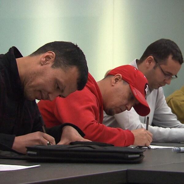 Des immigrants, tous des hommes, écrivent assis à une longue table.
