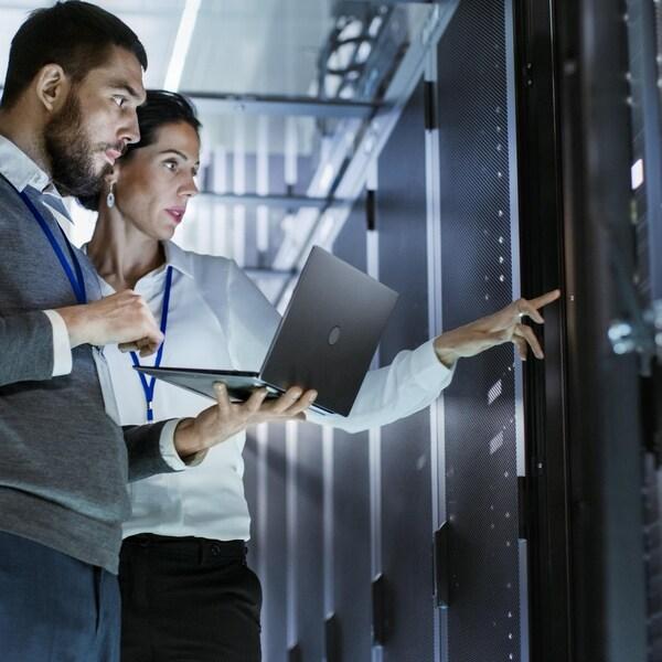 Un travailleur  est debout  et il tient dans la paume de sa main gauche un petit ordinateur portatif. Une femme pointe du doigt des données d'un serveur informatique et discute avec l'homme.
