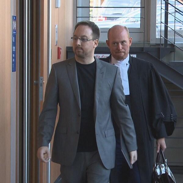 Jonathan Bettez et son avocat dans un couloir.