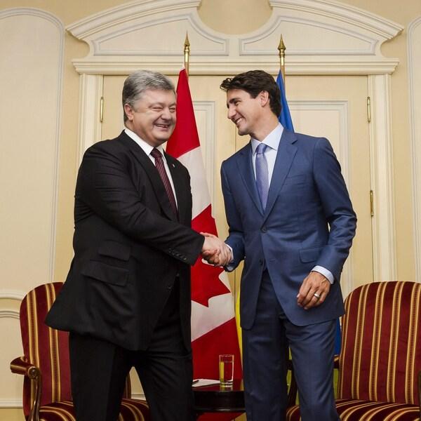 Le président ukrainien Petro Porochenko et le premier ministre canadien Justin Trudeau se serrent la main en souriant.
