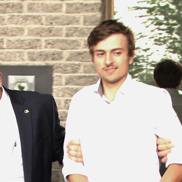 Un homme sourit à la caméra. Il est apporté par les enquêteurs.