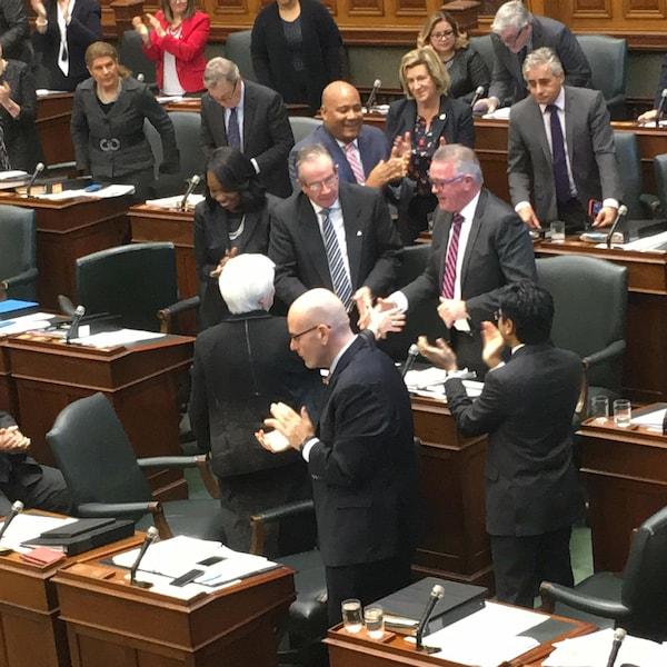Le ministre est debout en chambre et se fait serrer la main par une député, alors que les autres élus autour applaudissent.