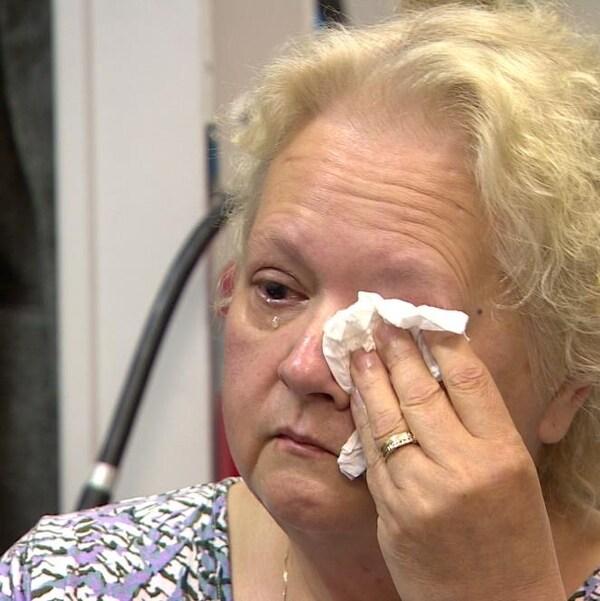 Gros plan sur les épaules et la tête d'une femme qui s'essuie l'oeil gauche avec un mouchoir alors qu'une larme coule de son oeil droit.