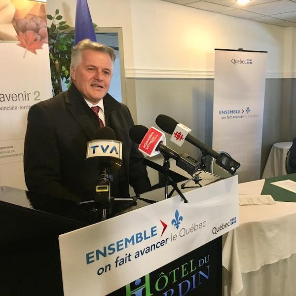 Le ministre parle au micro du podium de conférence de presse