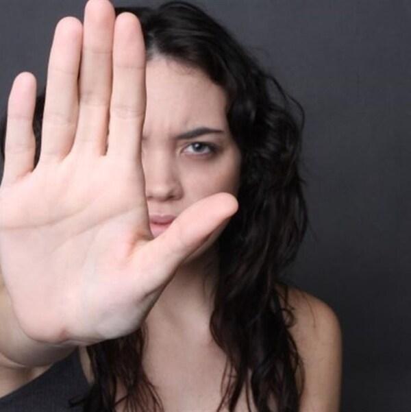 Une femme présente la paume de sa main en guise de halte devant son visage.