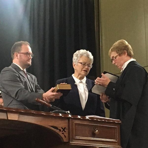 Antoinette Perry prête serment à la reine, une main sur la Bible.