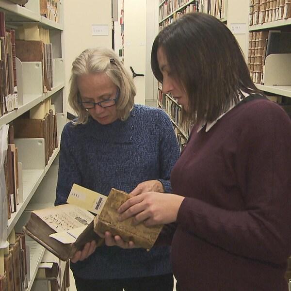 Deux femmes consultent des livres anciens.