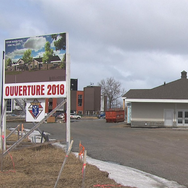Une affiche indique l'ouverture en 2018. Derrière, on peut voir une maison grise en construction.