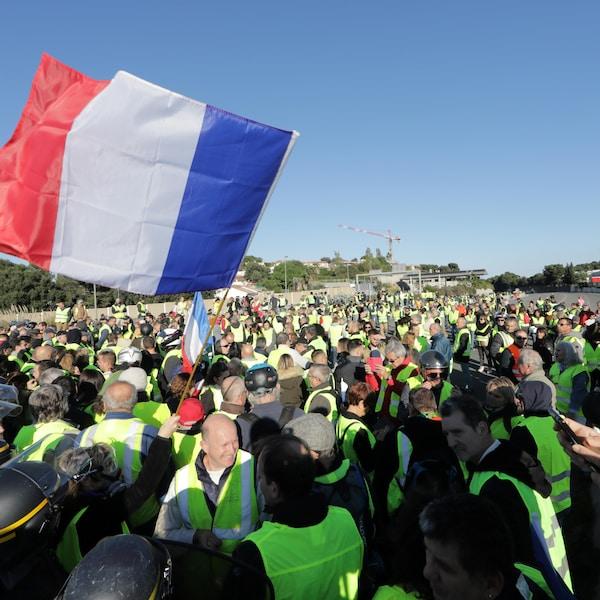 Des manifestants avec des gilets jaunes qui agitent le drapeau français et face à eux, des gendarmes anti-émeute.