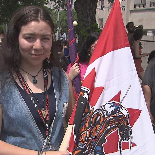 Une adolescente micmaque tient un drapeau canadien avec des symboles autochtones au milieu d'une foule.