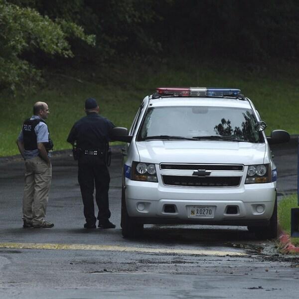 Des policiers se tiennent debout près d'un véhicule de police.