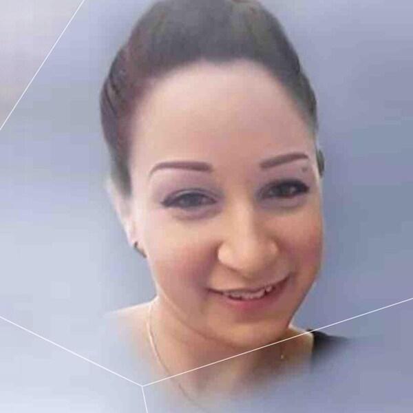 Une femme sourit à la caméra.