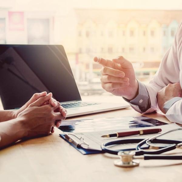 Un médecin est assis à son bureau et discute avec une patiente.