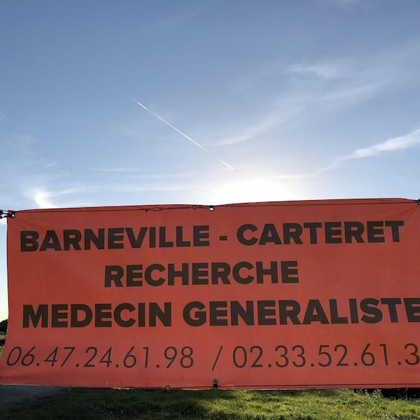 Affiche sur laquelle on peut lire : « Barneville-Carteret recherche médecine généraliste » avec deux numéros de téléphone.