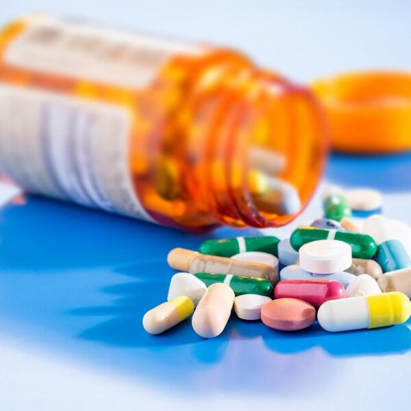 Des pilules de différentes couleurs à côté d'une bouteille de médicaments renversée.
