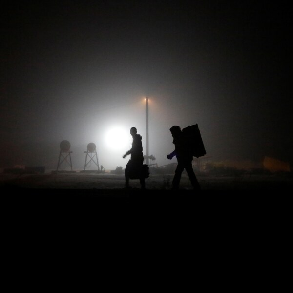 Deux hommes marchent sur des rails de chemin de fer en pleine nuit.