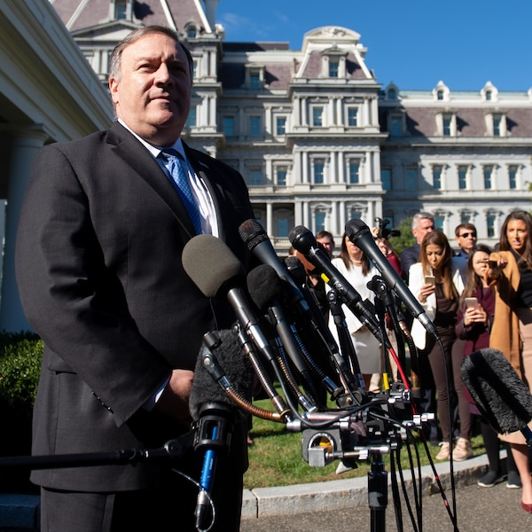 Mike Pompeo devant un trépied soutenant une dizaine de micros. Plusieurs journalistes écoutent ses propos.