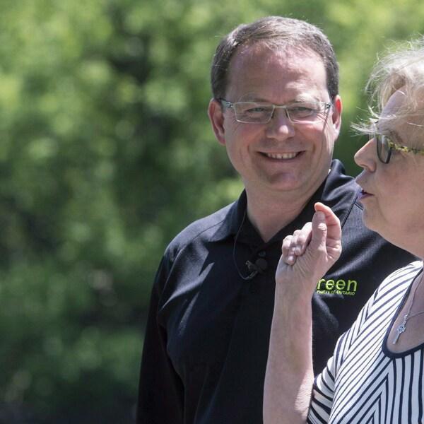 Mike Schreiner, portant un t-shirt noir, regarde Elizabeth May, vêtue d'une robe.