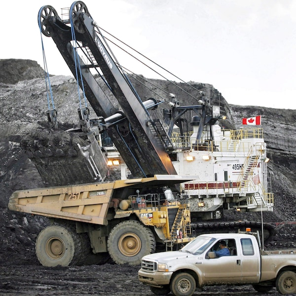 Une pelle minière remplit un camion de transport sur une mine de sables bitumineux près de Fort McMurray, en Alberta.