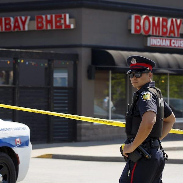 Photo d'un policier à côté d'une autopatrouille et d'une banderole de police jaune devant un restaurant