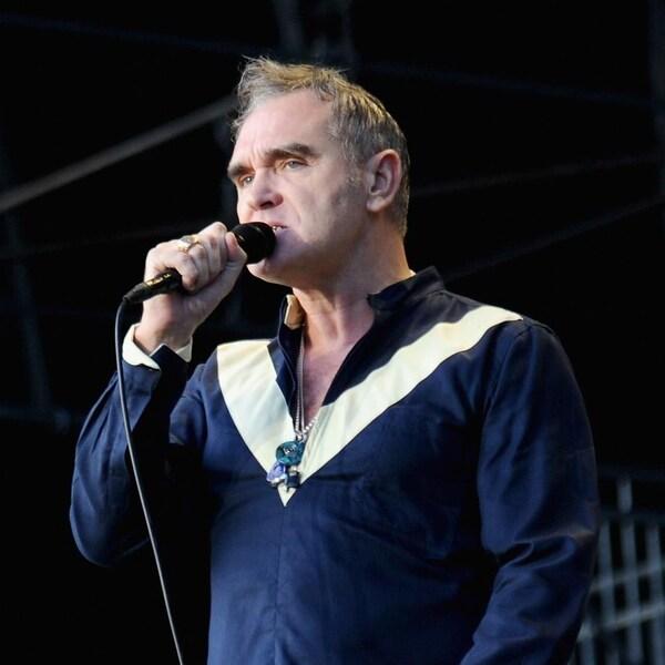 Le chanteur Morrissey tient un micro dans sa main droite et donne un spectacle devant une foule.