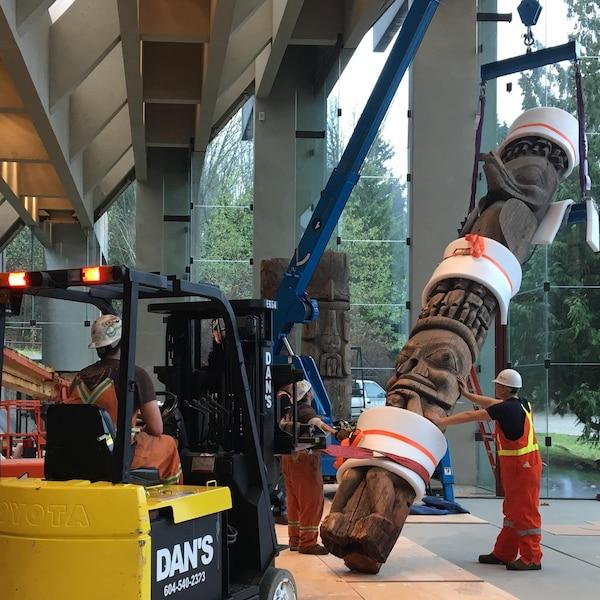 Des ouvriers descendent des totems à l'aide de machinerie.