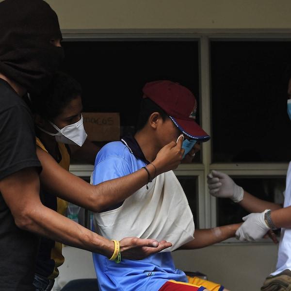Un jeune portant une casquette est aidé à marcher par trois autres personnes portant des masques et une cagoule.