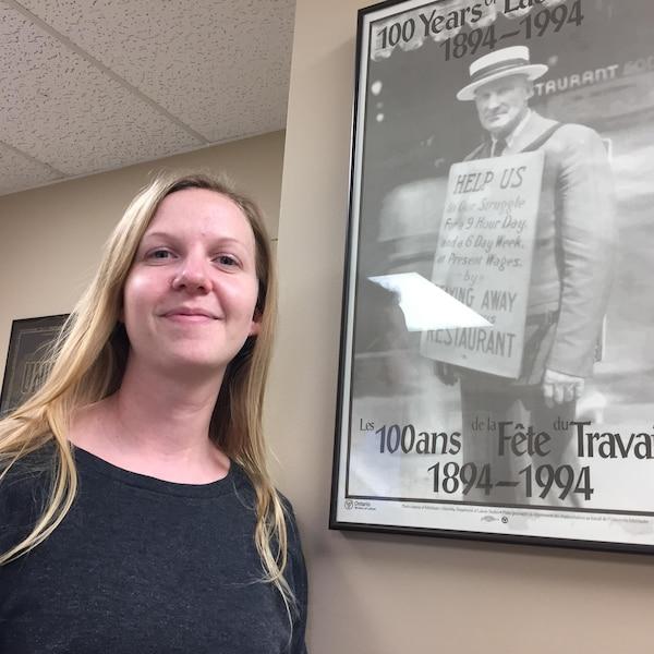 Nicole Ayotte devant une affiche soulignant les 100 ans de la Fête du travail.