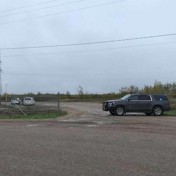 Une voiture de police est garée devant l'entrée d'un chantier industriel.