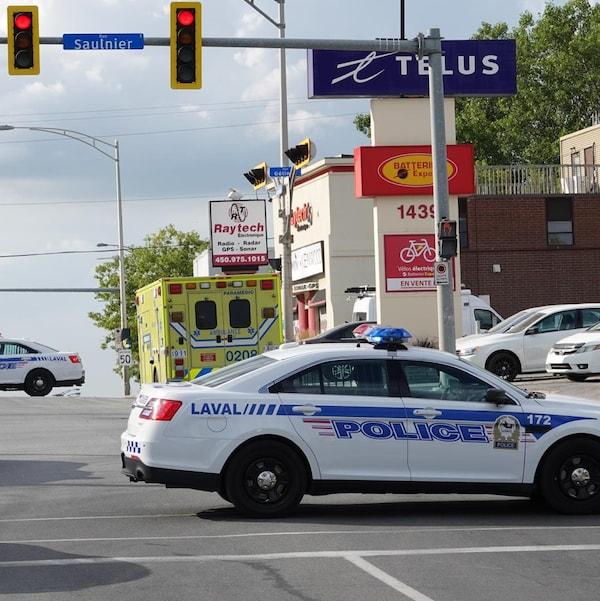 Nombreuses voitures de police dans une intersection à Laval
