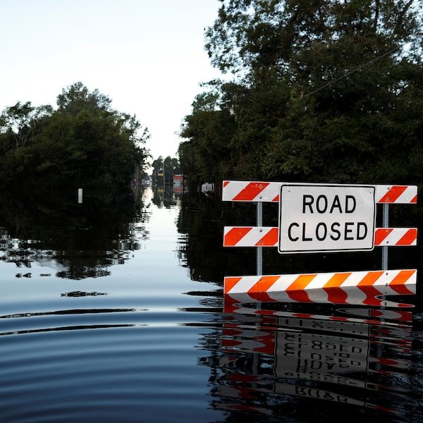 Une route sous les eaux, avec un panneau «road closed».