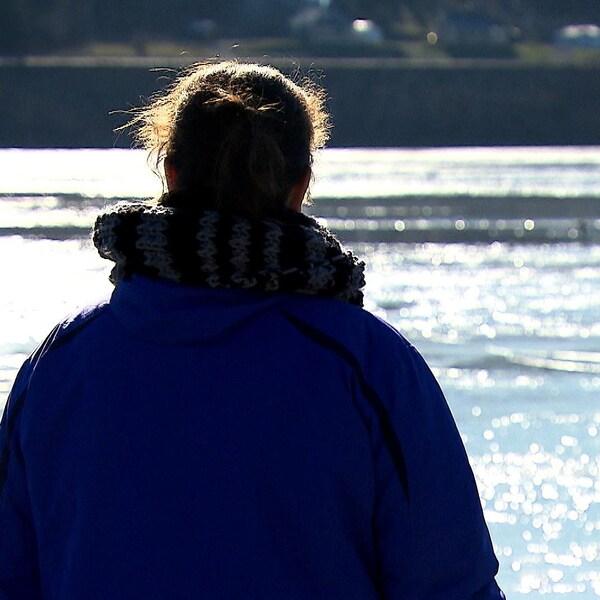 Une dame de dos face à une rivière.