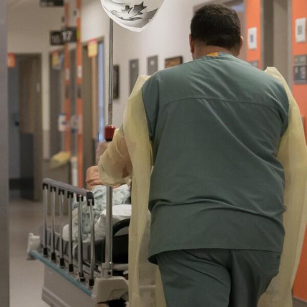 Un préposé au bénéficiaire pousse un patient sur une civière.