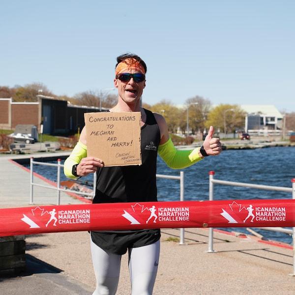 Patrick Charlebois qui s'apprête à franchir la ligne d'arriver, une bande rouge sur laquelle on peut lire Canadien Marathon Challenge
