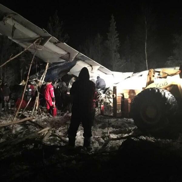Un avion écrasé au sol, des gens s'activent dans le noir