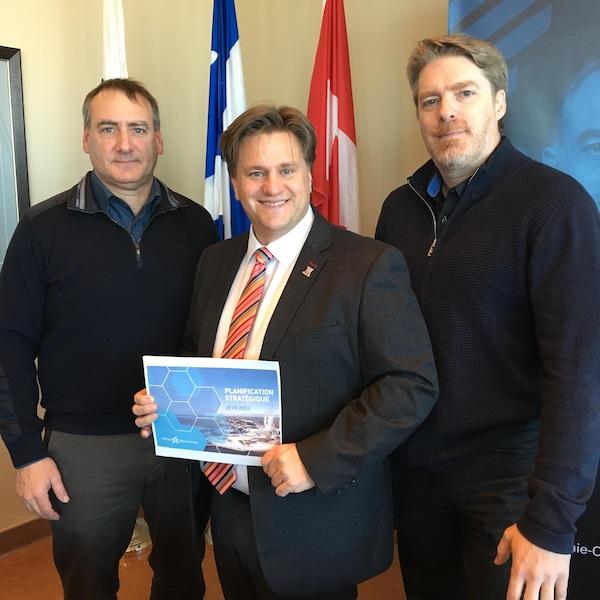 Le maire Yves Montigny tient le document résumant la planification stratégique de la ville pour 2018-2023.