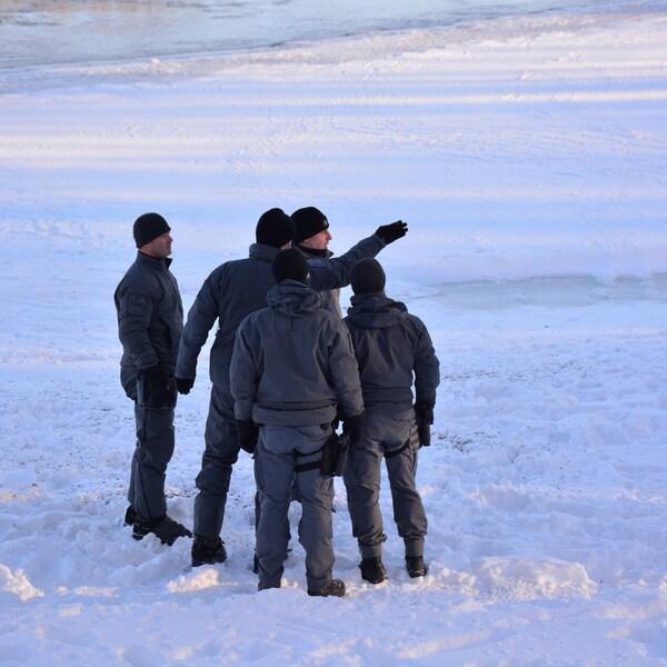 Cinq policiers se tiennent sur les berges de la rivière des Prairies.