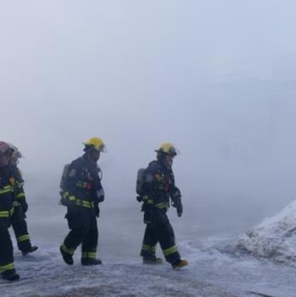 Des pompiers marchent dehors sous le froid et la fumée lors de l'incendie de la rue Roseberry à Winnipeg
